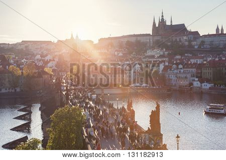 Charles Bridge on Vltava river in Prague, Czech Republic at sunset. View on Prague Castle, Hradcany. Sun flares.