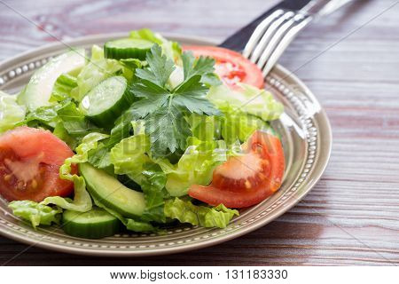 Diadonally a salad of lettuce, tomato, cucumber, avocado and cutlery on wood background. Healthy fresh salad for lunch. Horizontal. Daylight. Close.