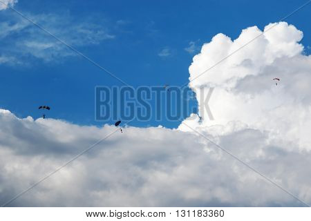 Four skydivers with open parachutes floating in the blue sky with clouds