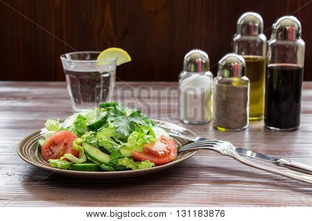 Left a salad of lettuce, tomato, cucumber, avocado, right fork with knife and on dark wood background a glass of water, salt, pepper, balsamic, olive oil. Healthy fresh salad for lunch. Horizontal.