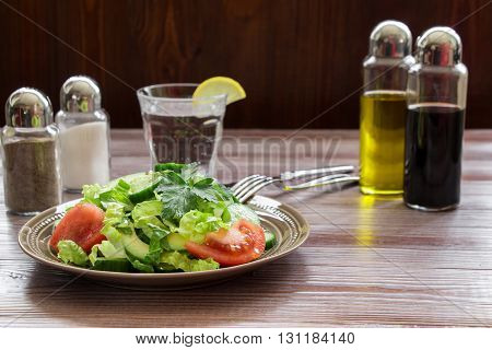 Left a salad of lettuce, tomato, cucumber, avocado in dark wood background a glass of water, salt, pepper, balsamic, olive oil, right down empty space for text. Vegan salad for lunch. Horizontal.