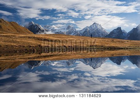 Beautiful landscape. Mountain Lake with mirrored reflection. Man stands on a hill. Koruldi Lake. Caucasus, Georgia, Zemo Svaneti
