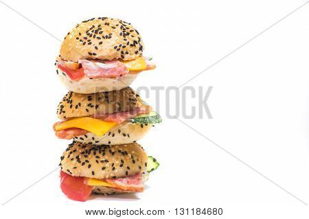 three hamburgers  with vegetables and bacon on a white background