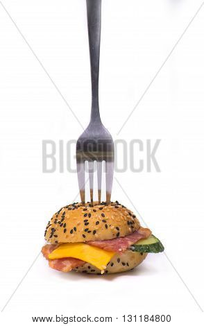 small hamburger  with vegetables and bacon under the fork on a white background