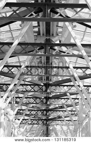 Glass ceiling footbridge with metal structures and circular lamps. Black and white photo.