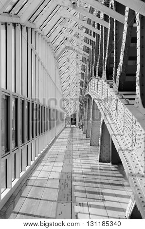 Indoor pedestrian bridge. Glass windows stretching into the distance. Perspective. A lot of repetitive elements. Pedestrian zone. Black and white photo.