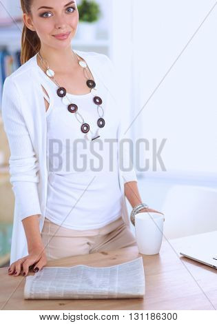 Young businesswoman standing near the desk with cup in office