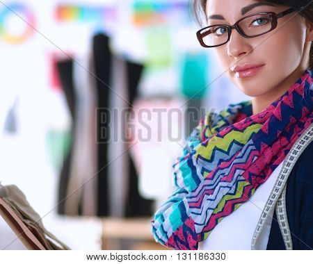 Beautiful fashion designer standing with folder in studio