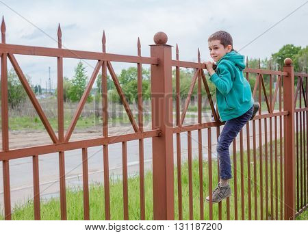 boy climbs up a high fence. concept escape from somewhere