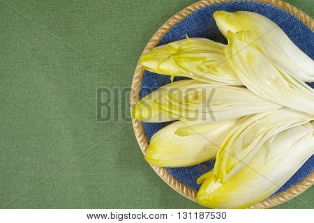 Fresh Chicory Salad leaves placed on a blue plate on green background copy space