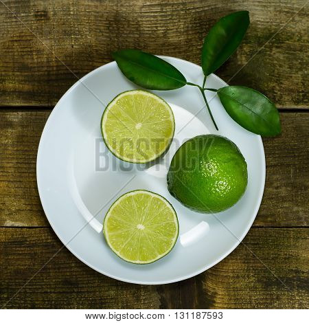 Lime in the white plate on wooden background