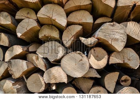 Pile of stacked firewood in rural garden ready for winter. Preparation for the winter. Wooden log abstract background. Dry chopped wood logs