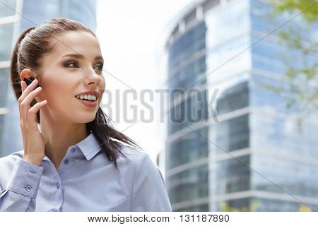 business, technology and people concept -  businesswoman with smartphone talking over office building