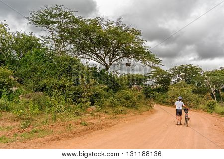 Rungwa Game reserve Tanzania - March 17 2015: Cyclist on the dirt road at the edge of Rungwa Game reserve in Tanzania.