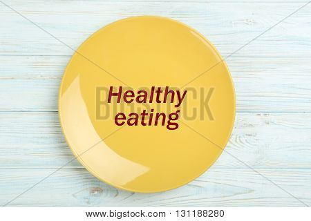 Yellow plate on a blue wooden table, healthy eating