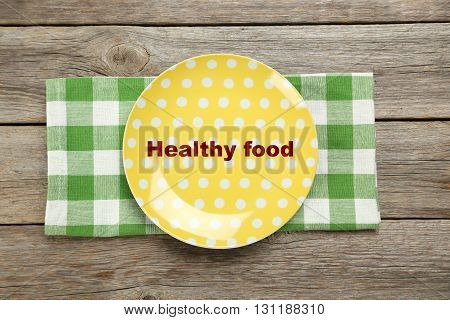 Yellow plate on a grey wooden table, healthy food