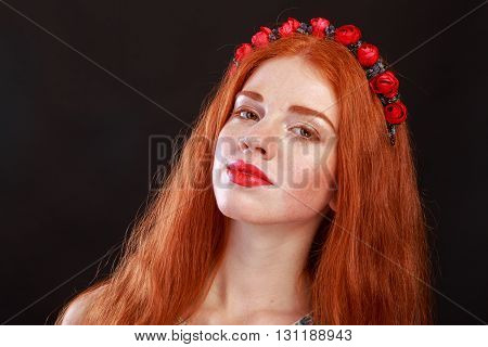 Beautiful red-haired girl with a wreath in her hair. Accessories for hair - wreaths. Hair ornaments. Gorgeous red-haired girl.