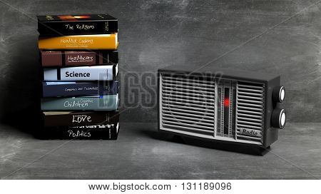 Antique radio transistor and stack of books with blackboard background. 3D rendering