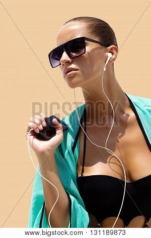 Dancing woman with headphones in black swimsuit and sunglasses poses on color background. High fashion look.