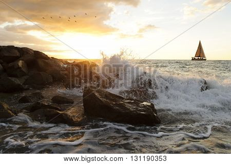 Sailing is a sailboat sailing along the sea with a wave breaking on the ocean rocks as a flock of birds fly in the sunset sky.
