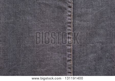 denim or rough cotton fabric or jeans material with the stitched seam for the textile textured background of dark color