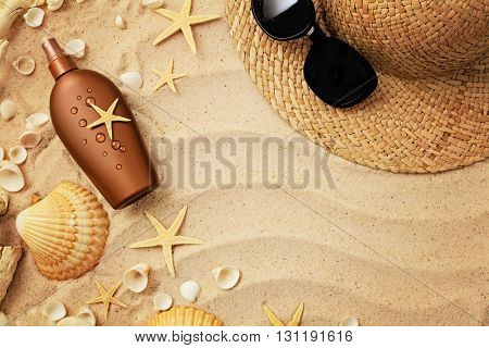 suntan cream bottle, summer straw hat and sunglasses on sand beach