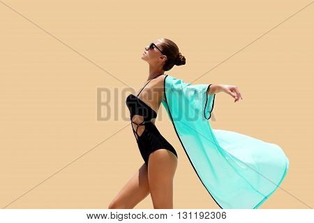 Dancing woman in black swimsuit sunglasses and turquoise beach dress poses on color background. High fashion look.  Hair up