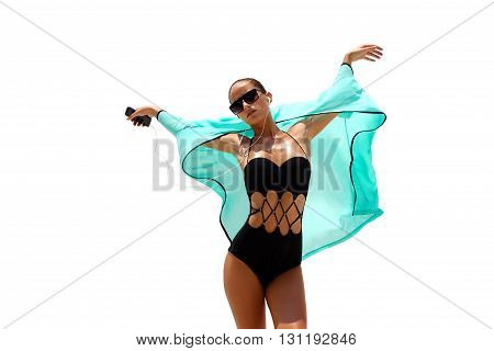 Dancing woman with headphones in black swimsuit and sunglasses poses on white isolated background. High fashion look.