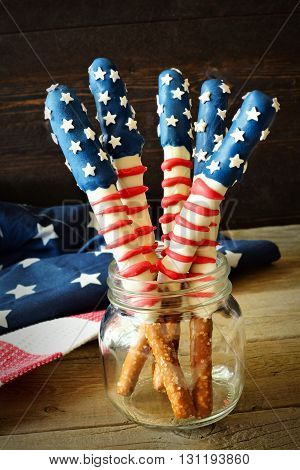 Fourth Of July American Flag Themed Pretzel Rods In A Mason Jar Against Rustic Wood