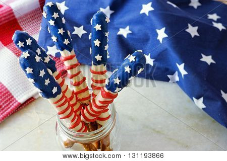 Fourth of July American flag themed pretzel rods in a mason jar with decor