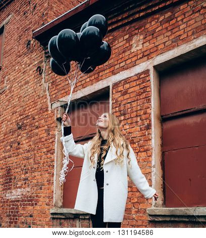 Beauty blonde girl in a white coat with black balloons