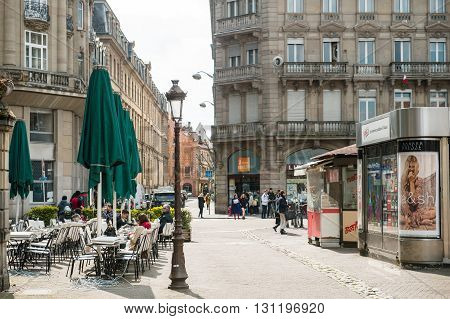 STRASBOURG FRANCE - APR 19 2016: Place Broglie with people enjoying afternoon cafe at terace press kiosk selling magazines and people commuting