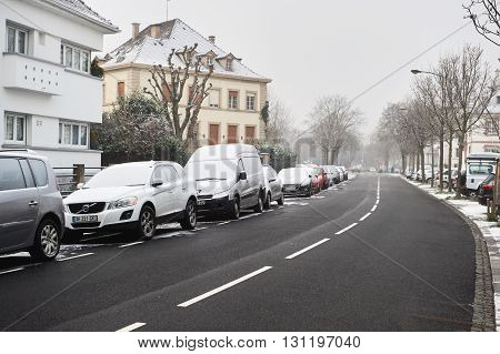 STRASBOURG FRANCE - JAN 20 2016: Winter snow in the city of Strasbourg Alsace France with cars and houses covered with snow and cleaned asphalt