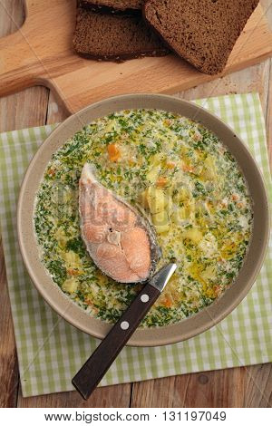 Finnish fish soup kalakeitto with salmon and cream on a rustic table