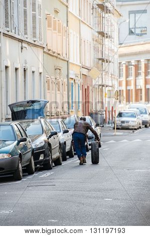 Rear view of man changing a wheel tyre of a modern car directly on the street