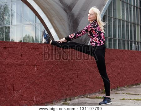 Street workout. Young blonde woman is doing leg stretching outdoors warming up before training