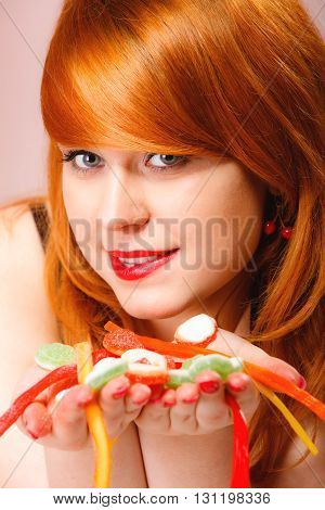 Sexy young woman holding candy. Redhair cute funny girl with sweet jelly on pink