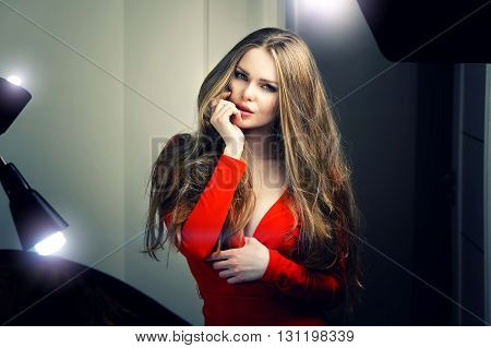 Beautiful sexy young caucasian woman in red dress and deep blue eyes looking straight into the camera. Backstage dramatic studio shot.