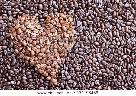 Background made from overhead view of heart shaped pile of coffee beans inset among darker ones spread across a surface