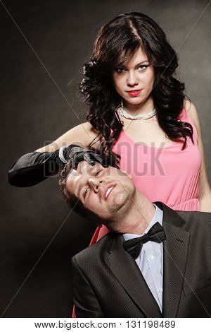 Woman in control of man sexy female controls her guy. Studio shot on black grey background.