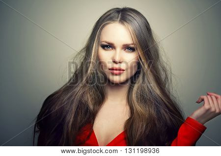 Beautiful young and emotional caucasian woman model with deep blue eyes and sensitive lips posing at studio in the light flashes. Great long natural hair.