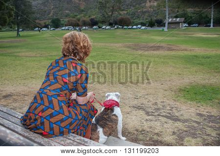 Over shoulder view of woman and dog seated on park bench.