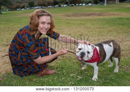 English Bulldog and smiling woman playing tug of war with stick.