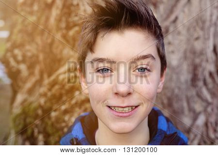 portrait of a smiling teenage boy with blue plaid lumberjack jacket