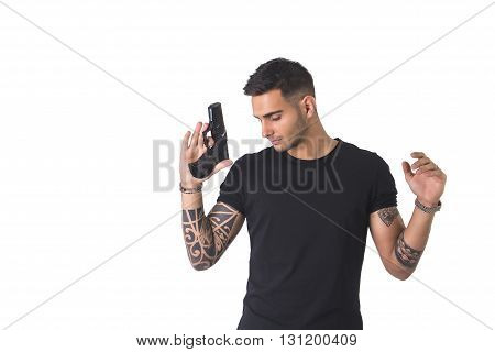 Portrait of detained tattooed man with gun. Studio shot. Isolated on white background.