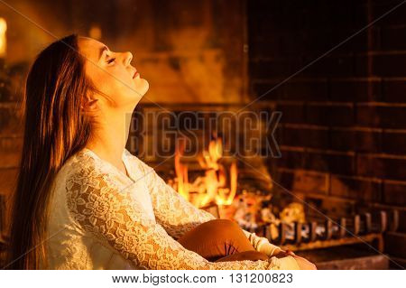 Woman relaxing resting at fireplace. Young girl heating warming up. Winter at home.