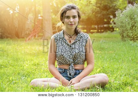 Beautiful Teenage Girl Sitting On A Meadow
