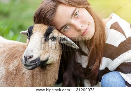 woman is stroking a brown sheep in summer