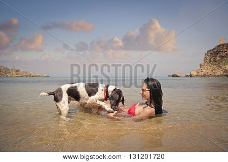 Happy girl playing with her dog at the beach