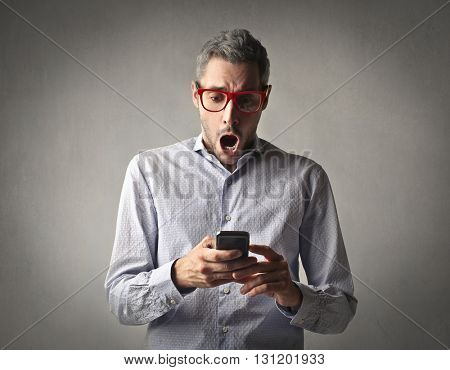 Shocked man checking his phone
